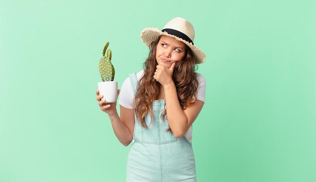 Młoda ładna kobieta myśli, czuje się zwątpienie i zdezorientowana i trzyma kaktusa