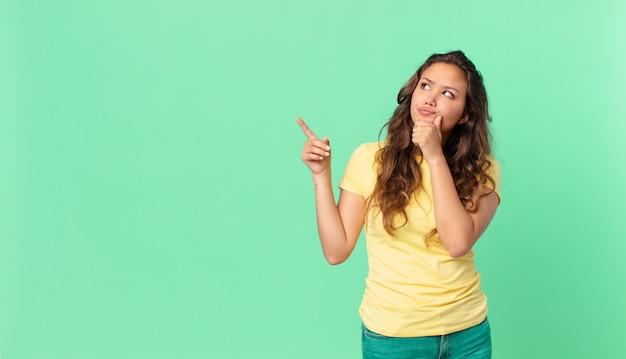 Młoda ładna kobieta myśli, czuje się zwątpienie i zdezorientowana i wskazuje na przestrzeń kopii