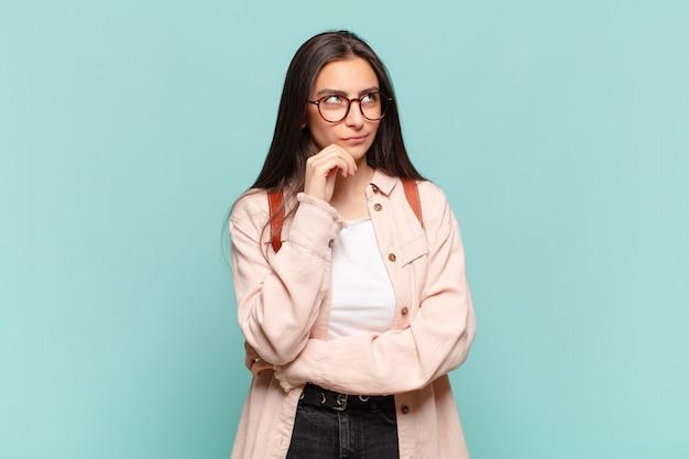 Młoda ładna kobieta myśli, czuje się zwątpienie i zdezorientowana, z różnymi opcjami, zastanawiając się, którą decyzję podjąć
