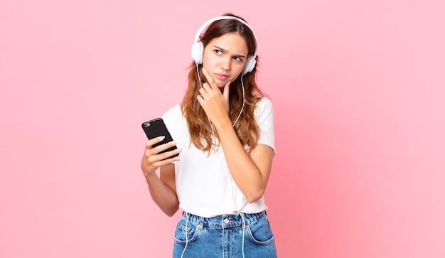 Młoda ładna kobieta myśli, czuje wątpliwości i jest zdezorientowana ze słuchawkami i smartfonem