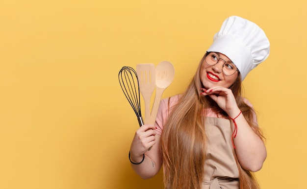 Młoda ładna Kobieta Myśli Lub Wątpi W Koncepcję Szefa Kuchni Premium Zdjęcia