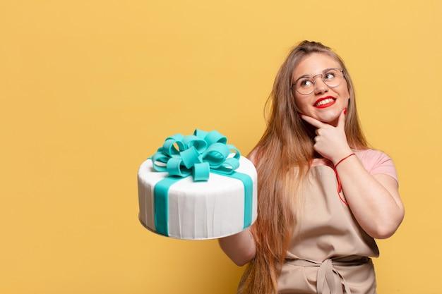 Młoda ładna kobieta myśli lub wątpi w koncepcję tort urodzinowy wyrażenie