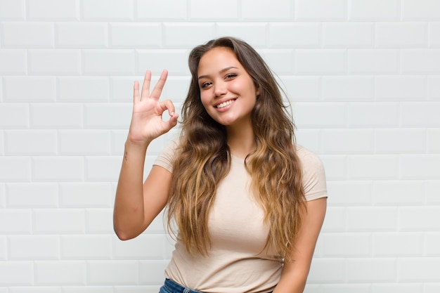 Młoda ładna kobieta na białej ścianie