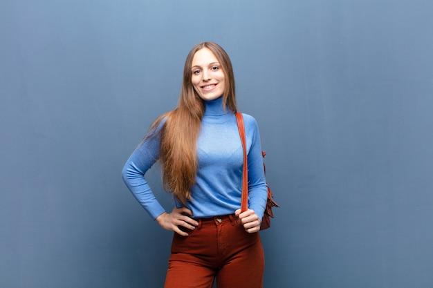 Młoda ładna kobieta na błękit ścianie z odbitkową przestrzenią
