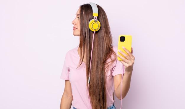 Młoda ładna kobieta na myślenie, wyobrażanie sobie lub marzy o widoku profilu. słuchawki i smartfon