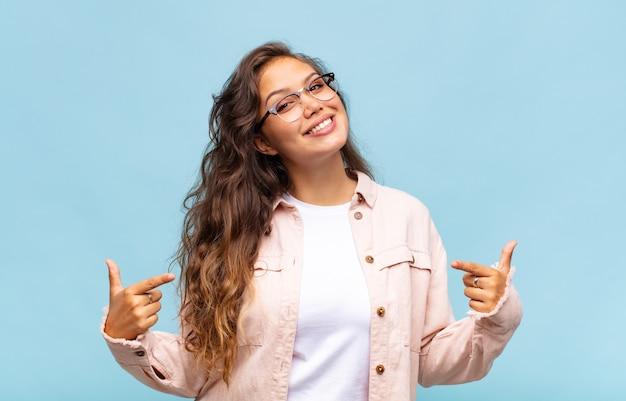 Młoda ładna kobieta na niebieskim tle w okularach