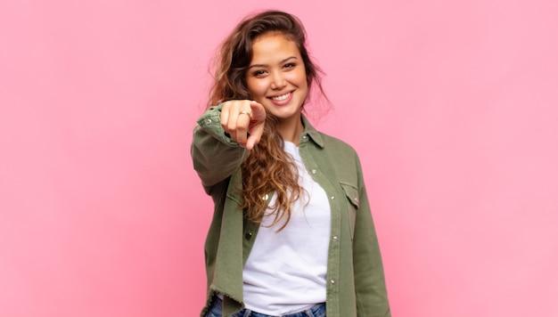 Młoda ładna kobieta na różowym tle, wskazując bezpośrednio