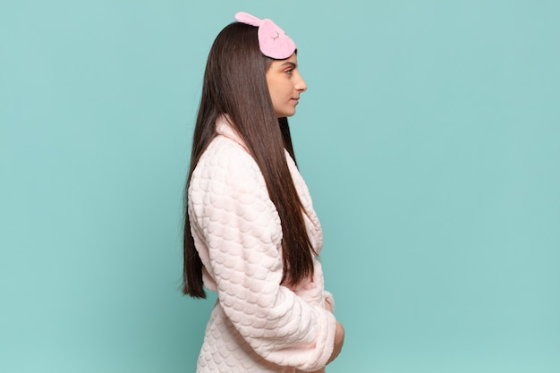 Młoda ładna kobieta na widoku profilu, chcąc skopiować przestrzeń do przodu, myśląc, wyobrażając sobie lub marząc. budząc się w koncepcji piżamy!