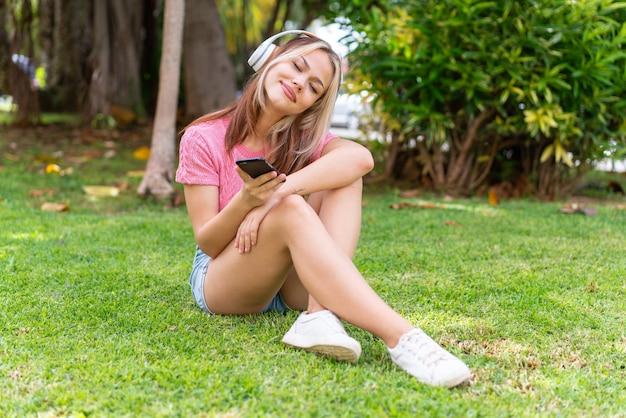 Młoda ładna kobieta na zewnątrz słucha muzyki z telefonu komórkowego