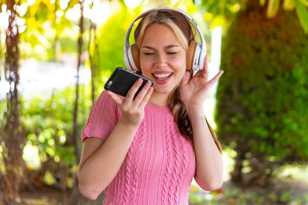 Młoda ładna kobieta na zewnątrz słucha muzyki za pomocą telefonu komórkowego i śpiewa
