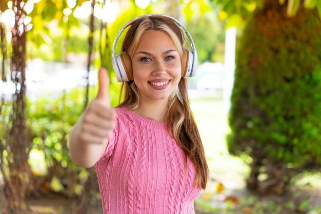 Młoda ładna kobieta na zewnątrz, słuchając muzyki i z kciukiem do góry