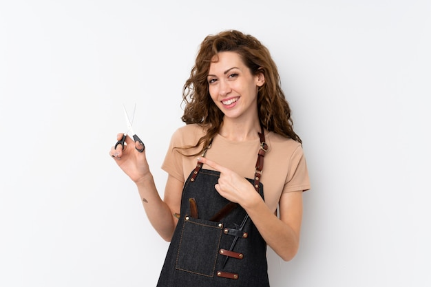 Młoda ładna kobieta nad odosobnioną ścianą z fryzjerem lub fryzjera męskiego suknią i wskazywać je