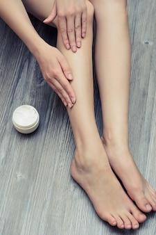 Młoda ładna kobieta nakłada krem na nogi, aby uniknąć podrażnień skóry