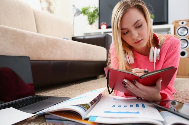 Młoda ładna kobieta nauki w salonie trzymać książkę w ramiona