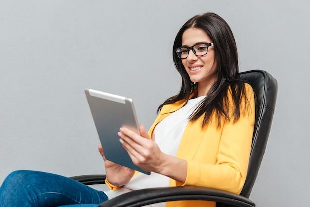 Młoda ładna kobieta nosi okulary i ubrana w żółtą kurtkę, siedząc na krześle biurowym podczas korzystania z komputera typu tablet na szarej powierzchni.