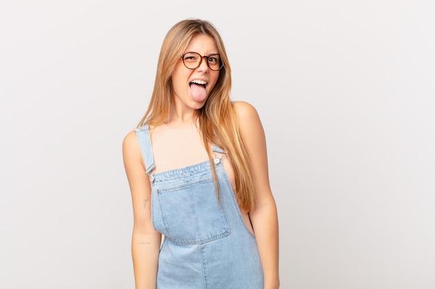 Młoda ładna kobieta o wesołej i buntowniczej postawie, żartująca i wystawiająca język tongue