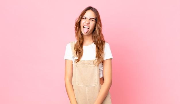 Młoda ładna kobieta o wesołej i buntowniczej postawie, żartująca i wystawiająca język