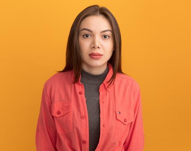 Młoda ładna kobieta odizolowana na pomarańczowej ścianie z miejscem na kopię