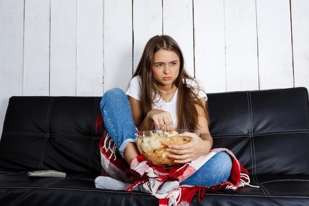 Młoda ładna kobieta ogląda tv, siedzi na kanapie w domu.
