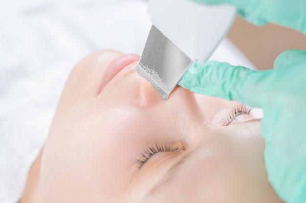 Młoda ładna kobieta otrzymujących zabiegi w salonach kosmetycznych. procedura czyszczenia ultradźwiękowego. kosmetologia sprzętowa. różne środki przekazu