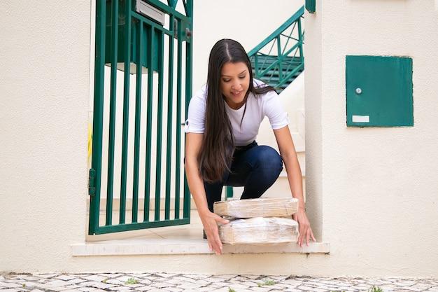 Młoda ładna kobieta otrzymuję zamówienie od wejścia. długowłosy klient latynoski kucający, uśmiechnięty i biorący kartony obiema rękami. dostawa i koncepcja zakupów online