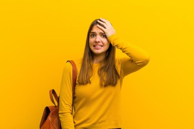 Młoda ładna kobieta panikuje nad zapomnianym terminem, czuje się zestresowana, musi ukryć bałagan lub błąd na pomarańczowo