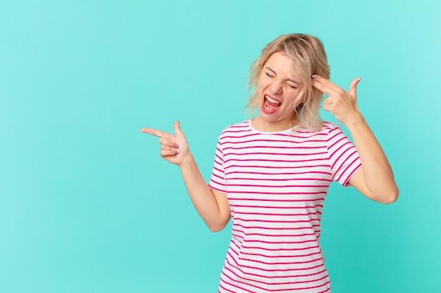 Młoda ładna kobieta patrząc niezadowolony i zestresowany, gest samobójczy co pistolet znak. kopia koncepcja przestrzeni