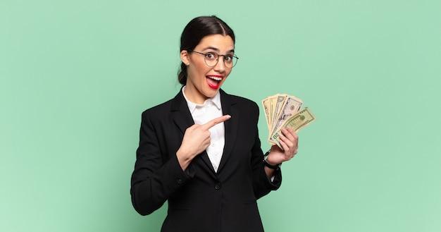 Młoda ładna kobieta patrząc podekscytowany i zaskoczony, wskazując na bok i do góry, aby skopiować przestrzeń. koncepcja biznesu i banknotów