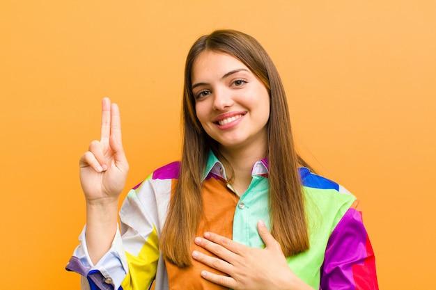 Młoda ładna kobieta, patrząc szczęśliwy, pewny siebie i godny zaufania, uśmiechając się i pokazując znak zwycięstwa, z pozytywnym nastawieniem na białym tle na płaskiej ścianie