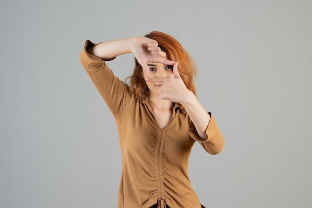 Młoda ładna kobieta patrząca przez palce do kamery na szarej ścianie