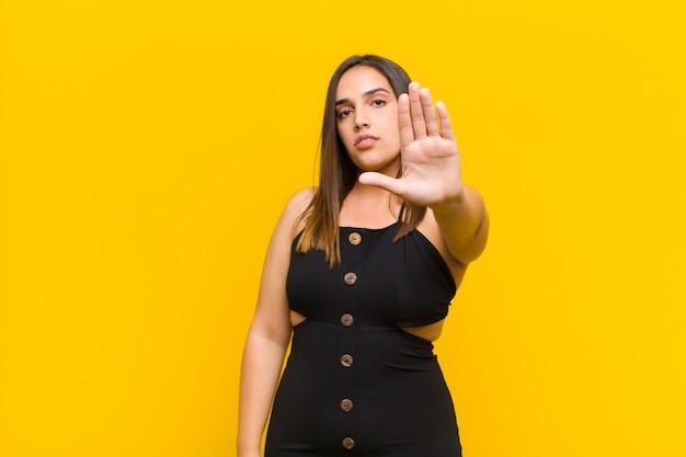 Młoda ładna kobieta patrzeje poważnego, srogiego, niezadowolonego i gniewnego seansu otwartej dłoni robi zatrzymanie gestowi odizolowywającemu przeciw pomarańcze ścianie