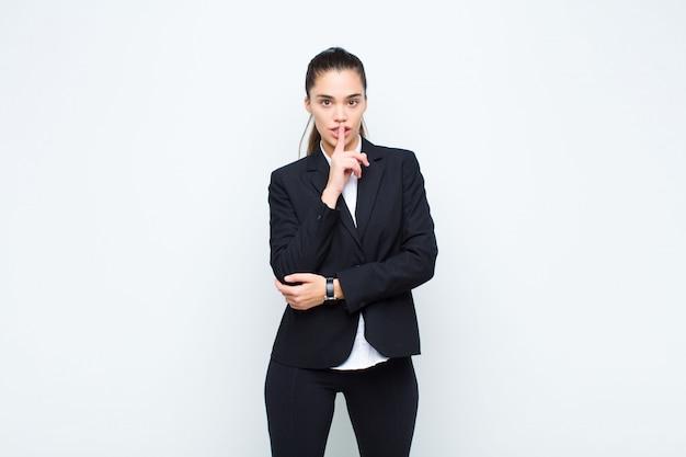 Młoda ładna kobieta patrzeje poważnie i krzyżuje z palcem naciskającym wargi wymagający ciszę lub ciszę, utrzymujący tajnego biznesowego pojęcie