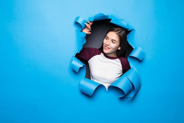 Młoda ładna kobieta patrzeje przez błękitnej dziury w papier ścianie.