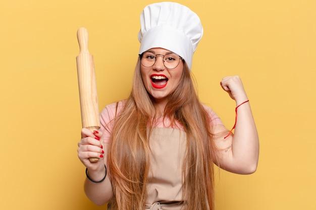 Młoda ładna kobieta piekarz z wałkiem do ciasta