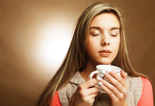 Młoda ładna kobieta pije kawę na beżowym tle