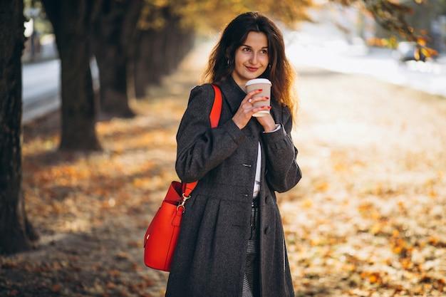 Młoda ładna kobieta pije kawę w parku