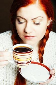 Młoda ładna kobieta pije kawę z bliska