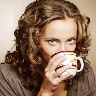 Młoda ładna kobieta pije kawę