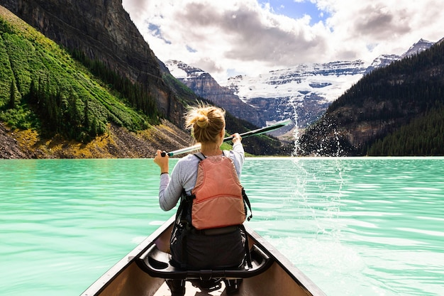 Młoda ładna kobieta pływająca kajakiem po jeziorze louise w kanadzie
