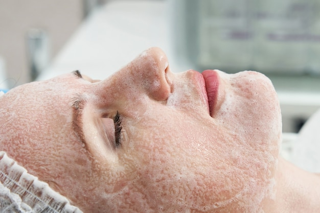 Młoda ładna kobieta poddawana zabiegom w salonach kosmetycznych przy użyciu pianki do mycia twarzy