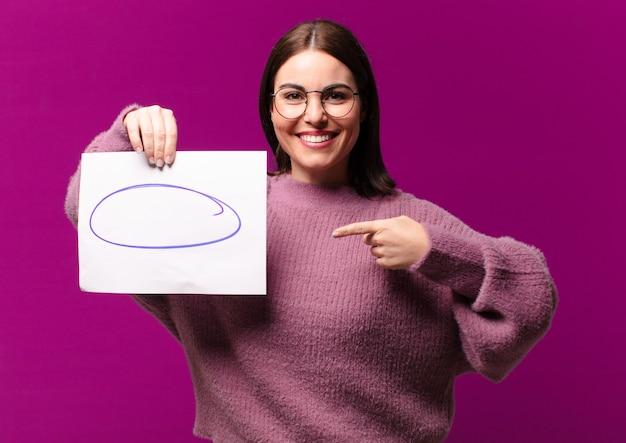Młoda ładna kobieta pokazuje kartkę papieru z uwagami
