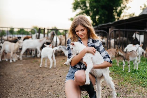 Młoda ładna kobieta pozuje na ranczo z kozami i innymi zwierzętami.