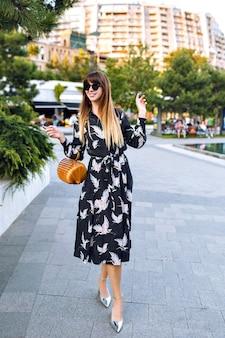 Młoda ładna kobieta pozuje na ulicy w centrum miasta, ubrana w elegancką długą sukienkę i modną torebkę ze słomy vintage, ciesz się atmosferą,