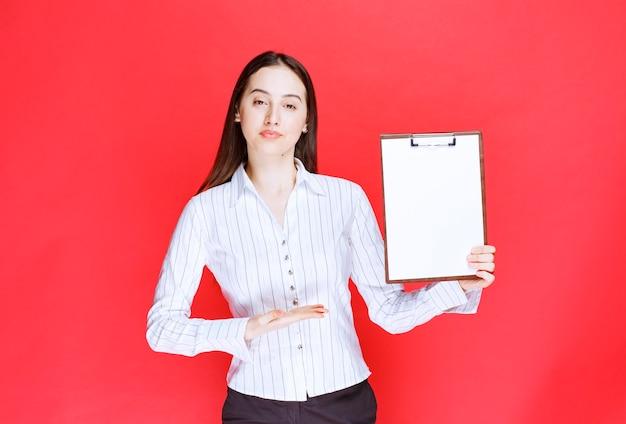 Młoda ładna kobieta pozuje z pustym schowkiem na czerwonej ścianie.
