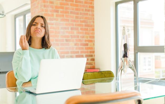 Młoda ładna kobieta pracująca, robiąca gesty lub pieniądze, każąca ci spłacić długi!