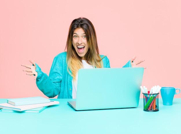 Młoda ładna kobieta pracująca z laptopem, czująca się szczęśliwa, zdziwiona, szczęśliwa i zaskoczona, lubiąca mówić poważnie? nie do wiary