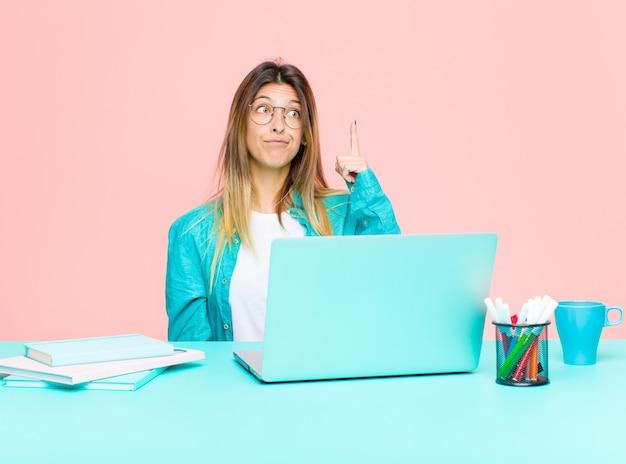 Młoda ładna kobieta pracująca z laptopem czuje się jak geniusz, który dumnie trzyma palec w powietrzu po zrealizowaniu świetnego pomysłu, mówiąc: eureka