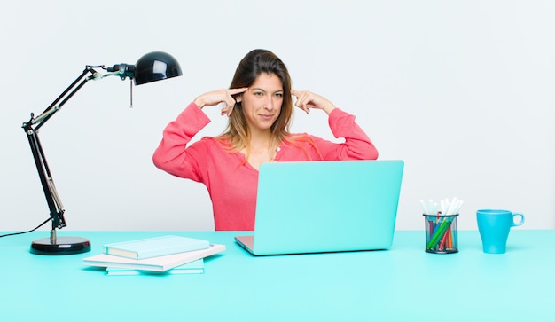 Młoda ładna kobieta pracująca z laptopem czuje się zagubiona lub wątpiąca, koncentrując się na pomyśle, ciężko myśląc, szukając miejsca na stronie