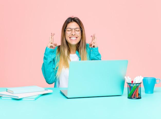 Młoda ładna kobieta pracująca z laptopem czuje się zdenerwowana i pełna nadziei, krzyżuje palce, modli się i ma nadzieję na szczęście