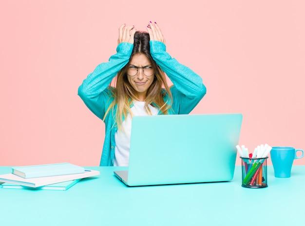 Młoda ładna kobieta pracująca z laptopem czuje się zestresowana i niespokojna, przygnębiona i sfrustrowana bólem głowy, podnosząc obie ręce do głowy